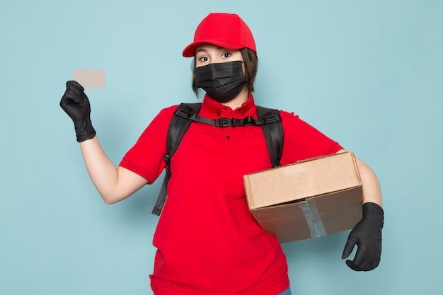 青のパッケージを保持している赤いポロ赤キャップ黒滅菌防護マスク黒バックパックの若い宅配便 無料写真