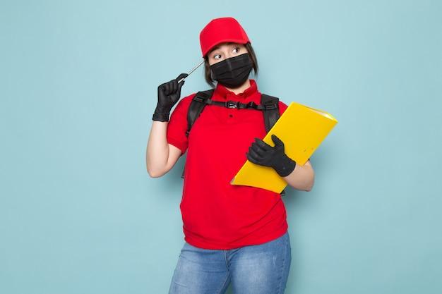 Молодой курьер в красной поло красная шапочка черная стерильная защитная маска черный рюкзак с пакетом Бесплатные Фотографии