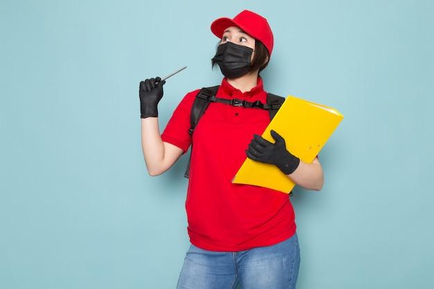 Молодой курьер в красной поло красная шапочка черная стерильная защитная маска черный рюкзак с пакетом желтых тетрадь на синем Бесплатные Фотографии