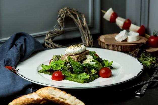 Рыбный котлет с салатом из латука, черным хлебом и помидорами Бесплатные Фотографии
