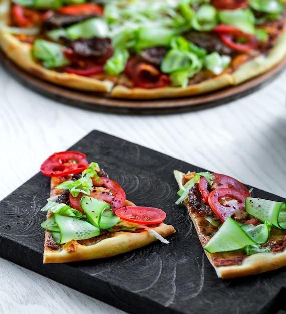 新鮮なキュウリとトマトのスライスと肉のピザ 無料写真