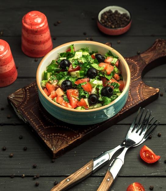 Чаша греческого салата с оливками, огурцами, помидорами и зеленью Бесплатные Фотографии