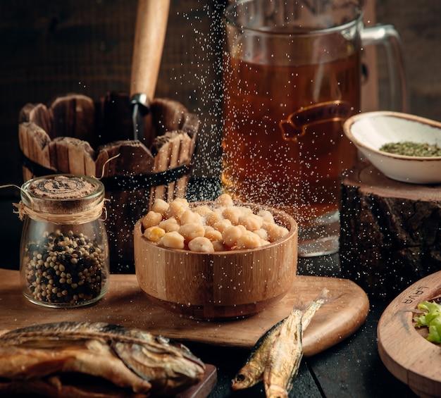 ひよこ豆のボウルには、ビールのセットアップのための塩が注がれています 無料写真