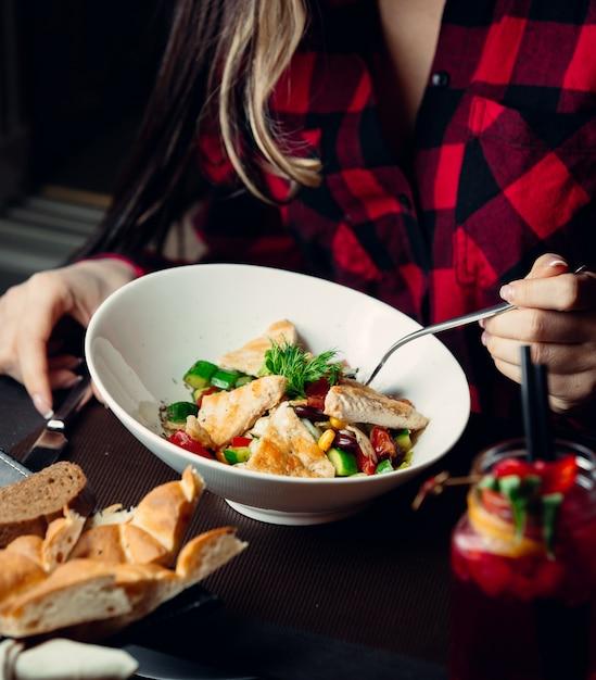 ゆで野菜とチキンサラダを食べる女性 無料写真
