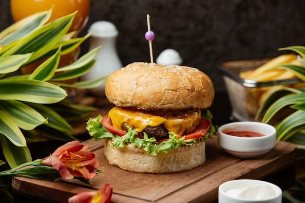 Бургер из говядины с листьями салата, чеддером, помидорами, майонезом и кетчупом Бесплатные Фотографии