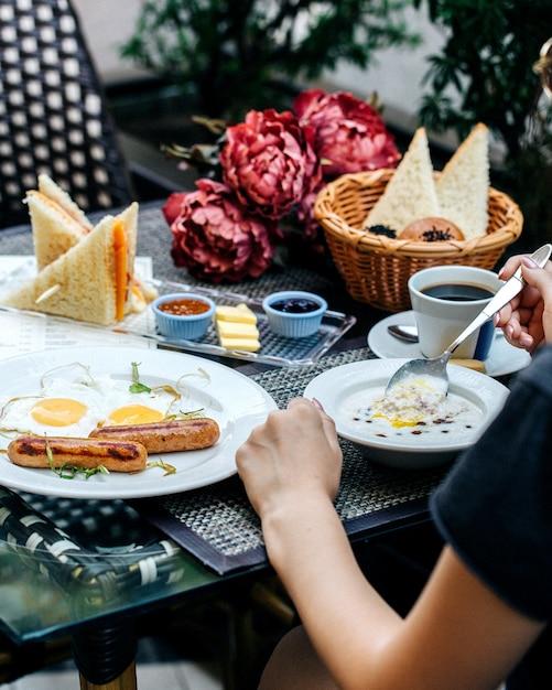 テーブルで朝食を食べている人 無料写真