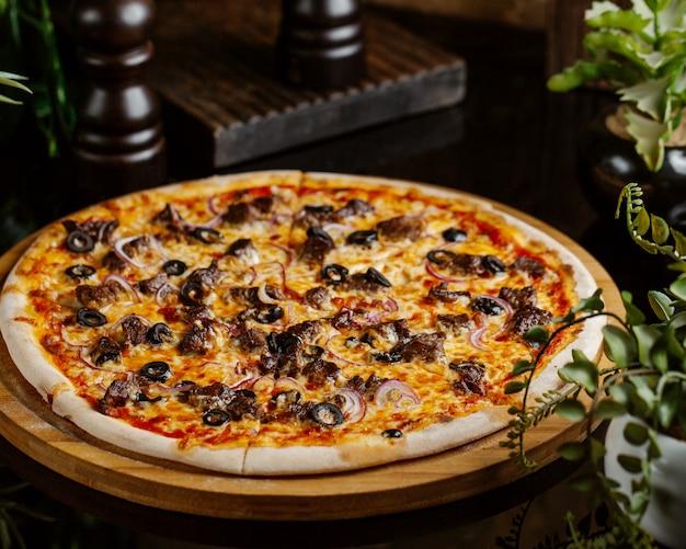 赤玉ねぎリング、オリーブ、チーズの肉ピザ 無料写真
