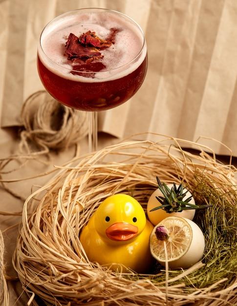 Красный коктейль, украшенный сушеными лепестками роз рядом с керамическим желтым утенком Бесплатные Фотографии