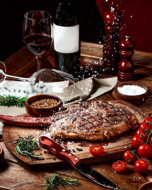 ワインを添えてビーフステーキの上に塩の振りかける 無料写真