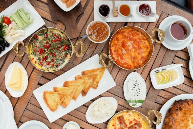 卵料理、パンケーキ、新鮮なサラダ、ジャム、チーズ、蜂蜜を含む伝統的なアゼルバイジャンの朝食 無料写真