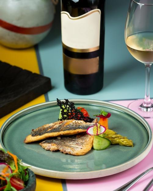 Жареная рыба с овощами и бутылка белого вина Бесплатные Фотографии
