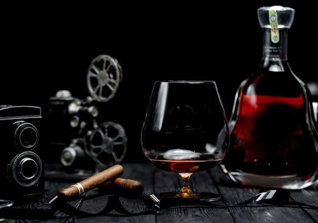 コニャックと木製のテーブルの葉巻のガラス 無料写真