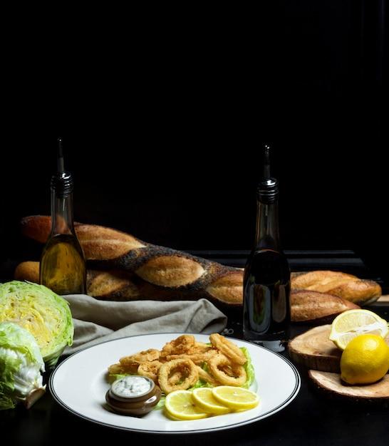 Луковые кольца в кляре с соусом и дольками лимона Бесплатные Фотографии