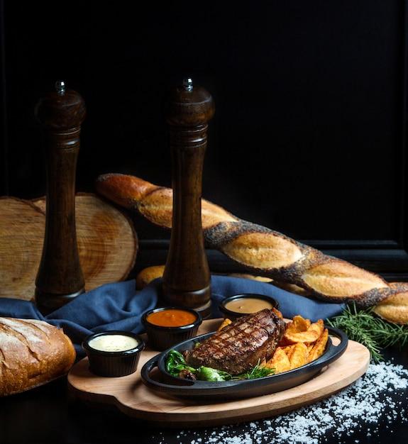Хорошо приготовленный стейк с домашней жареной картошкой и соусами Бесплатные Фотографии