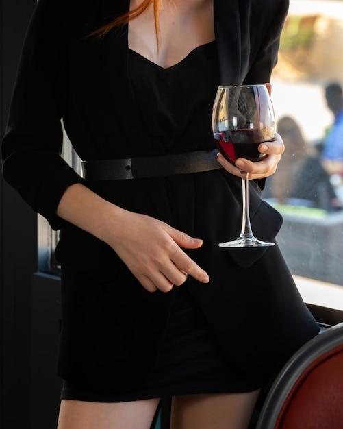 赤ワインのグラスと黒のドレスの女の子 無料写真