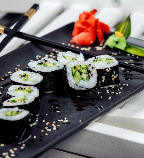 テーブルの上にご飯と黒の新鮮な寿司 無料写真