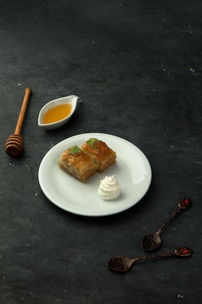 テーブルの上の蜂蜜とトルコのパクラバ 無料写真