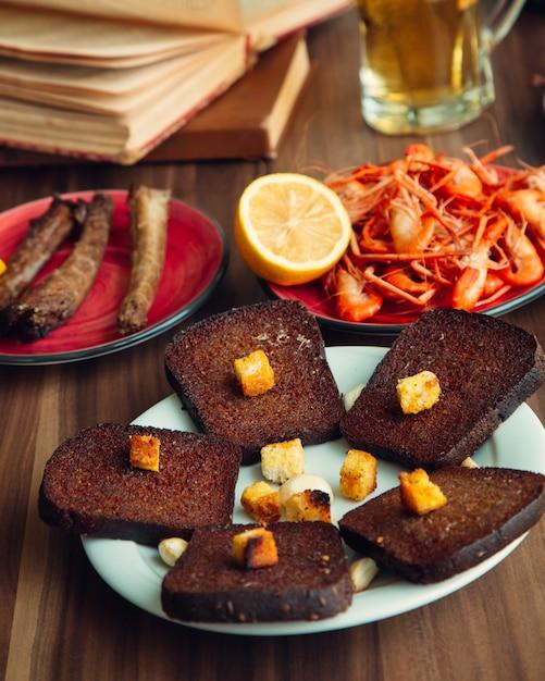 Тост из черного хлеба рядом с жареными креветками и лимоном Бесплатные Фотографии