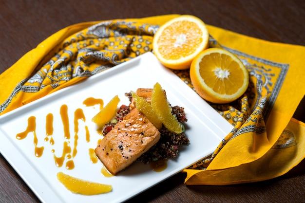 オレンジと赤米を添えたフライドサーモン 無料写真