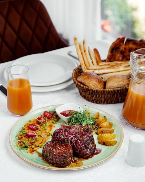 ポテト、ケチャップ、サラダを添えたトマトソースのグリルステーキ 無料写真