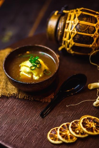 さいの目に切ったねぎを添えた中華スープのボウル 無料写真