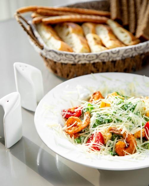 パンかご、塩、コショウを添えたエビのシーザーサラダのプレート 無料写真