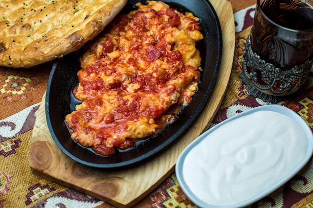 ヨーグルトとタンドールのパンを添えた卵とトマト料理の鋳鉄の盛り合わせ 無料写真