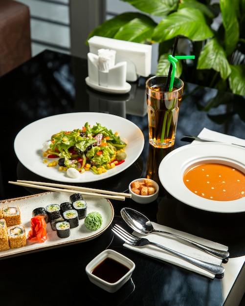 レンズ豆のスープ、新鮮野菜のサラダ、寿司プレートを使ったランチのセットアップ 無料写真