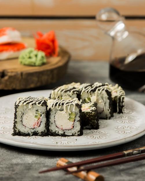 黒トビコで覆われたカニスティックとキュウリの巻き寿司 無料写真