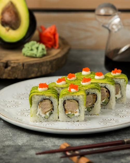 アバカド、クリーム、赤いトビコで覆われた寿司ロールのプレート 無料写真