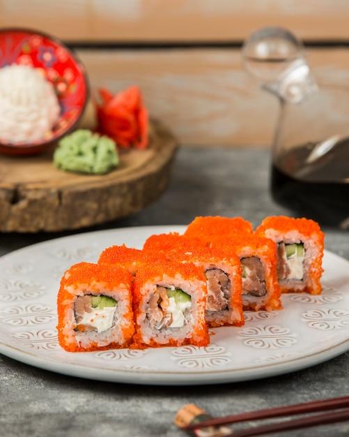 赤いトビコで覆われたサーモン、キュウリの巻き寿司 無料写真