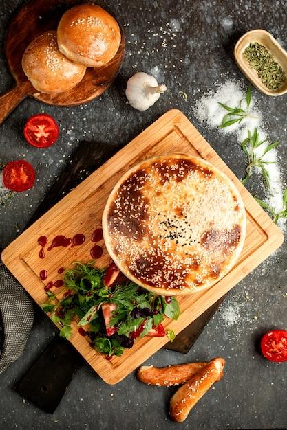 Воздушный хлеб, посыпанный кунжутом и помидорами с зеленью Бесплатные Фотографии