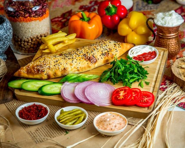 Пекарня с кунжутным топингом и различными нарезанными овощами Бесплатные Фотографии