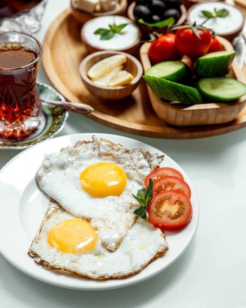 Жареное яйцо с чаем и овощами Бесплатные Фотографии