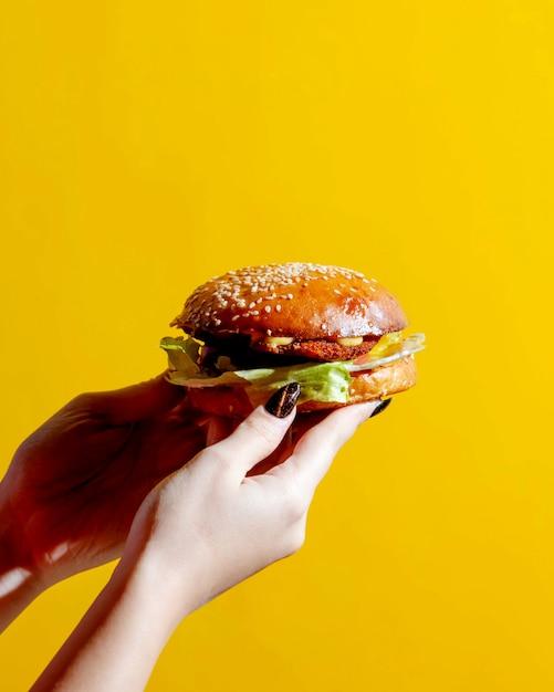 Женщина держит бургер в руках Бесплатные Фотографии