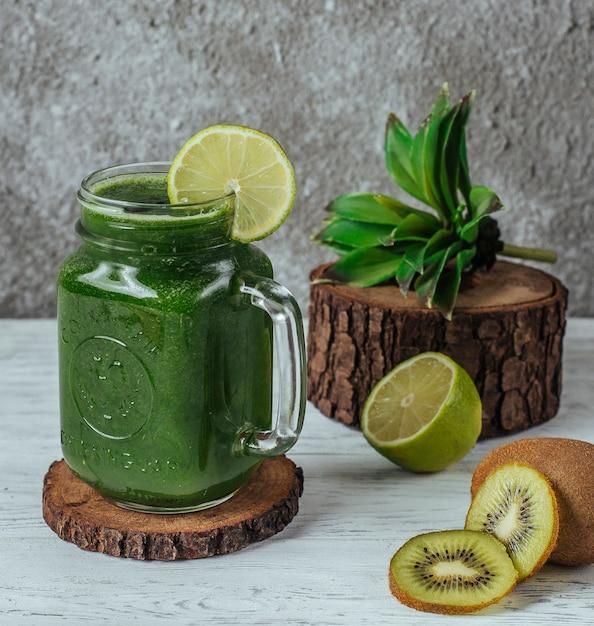 Зеленый коктейль в масонной баночке с ломтиком лайма, украшенный ломтиками киви Бесплатные Фотографии
