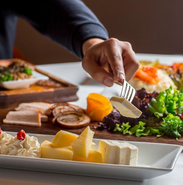 Человек берет сыр из сырной тарелки с белым сыром, чеддером, сливочным сыром Бесплатные Фотографии