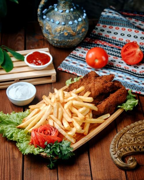 Жареные куриные наггетсы с картофелем фри на столе Бесплатные Фотографии