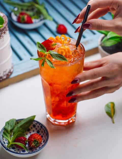 氷、イチゴ、オレンジの粒子とスターベリーとオレンジジュース 無料写真
