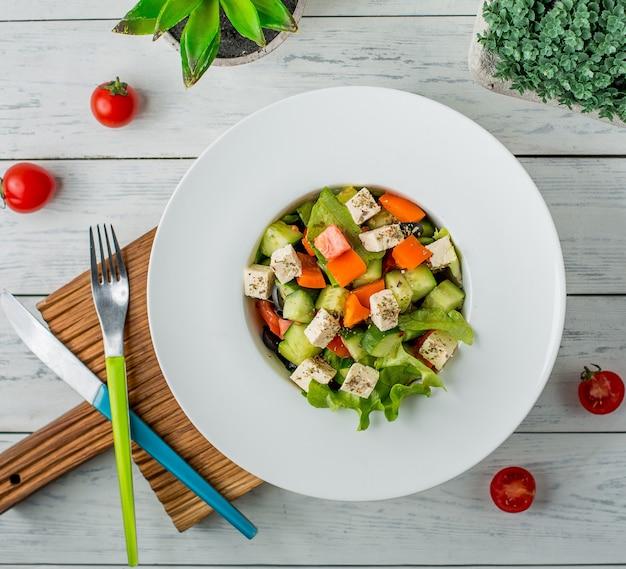 ピーマン、キュウリ、オリーブオイル、ホワイトチーズ、レタス、トマトの野菜サラダ 無料写真