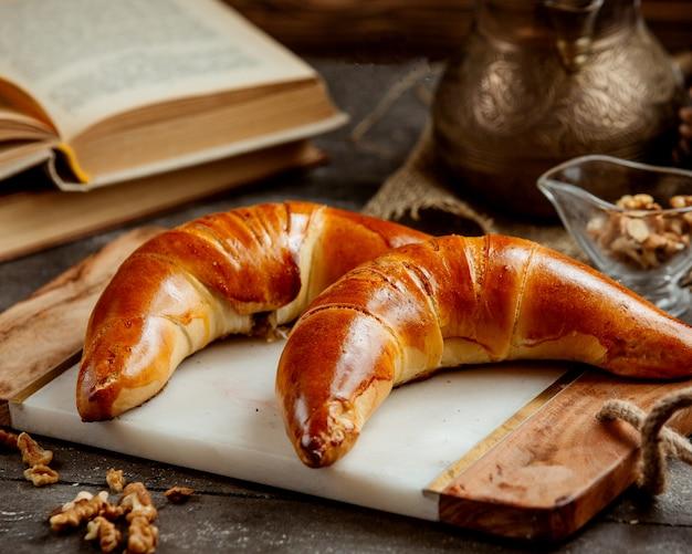 クルミと砂糖の混合物で満たされたバナナ型の甘いパン 無料写真
