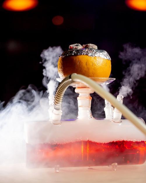 Дым выходит из грейпфрутового кальяна на стеклянной основе Бесплатные Фотографии