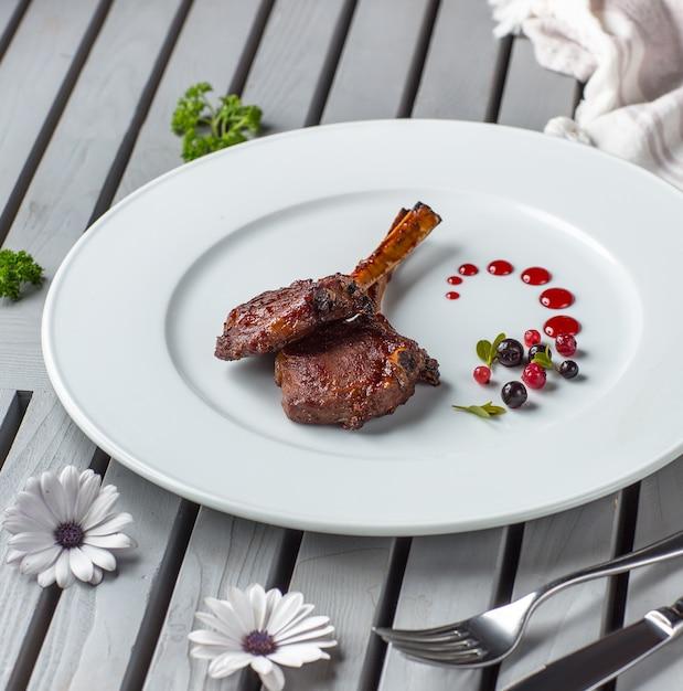 Два куска шашлыка из баранины в белом блюде с ягодным соусом Бесплатные Фотографии