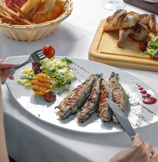 レタス、レモンとトマトのグリル焼き魚を食べる女性 無料写真