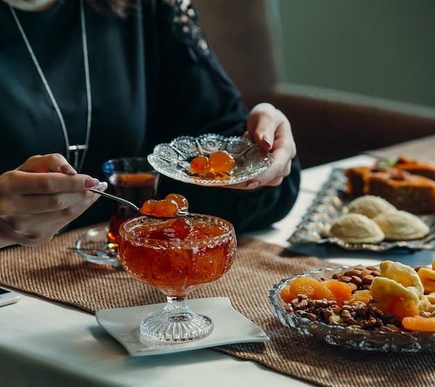 クリスタルポットからお茶の設定で受け皿にチェリージャムを取る女性 無料写真