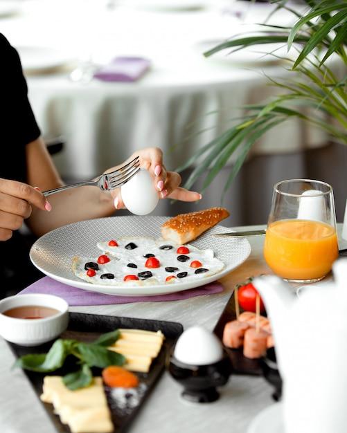 Женщина завтракает с вареным яйцом и яичным желтком, приготовленным с помидорами и оливками Бесплатные Фотографии