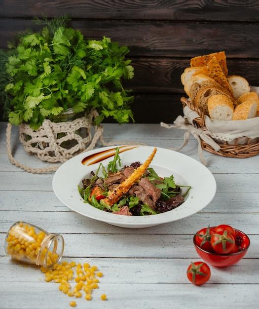 Салат из говядины с рукколой, помидорами, листьями салата и хлебной палочкой Бесплатные Фотографии