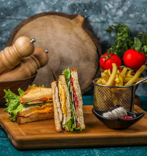 フライドポテト、マヨネーズ、ケチャップを木製のサービングボードで提供するクラブサンドイッチ 無料写真