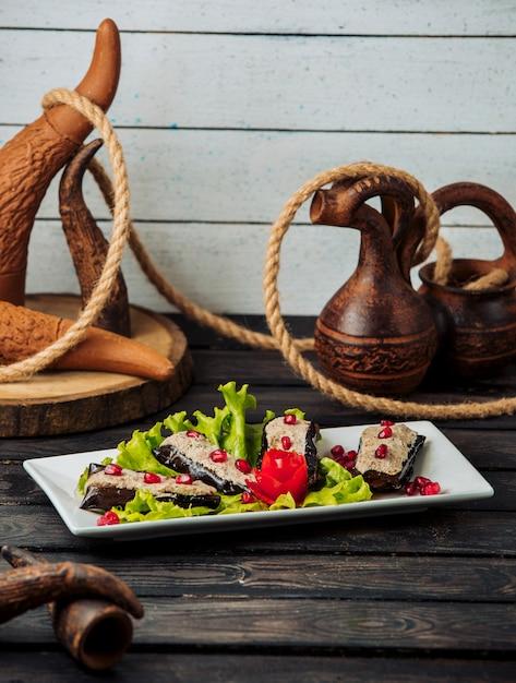 Жареные половинки баклажана, увенчанные смесью из курицы и грецкого ореха, украшенные гранатом Бесплатные Фотографии