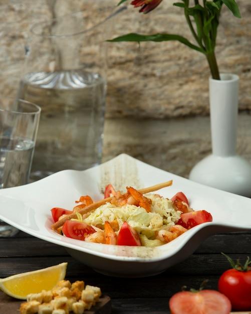 Салат из жареных креветок с листьями салата, ломтиком помидора и хлебной палочкой Бесплатные Фотографии